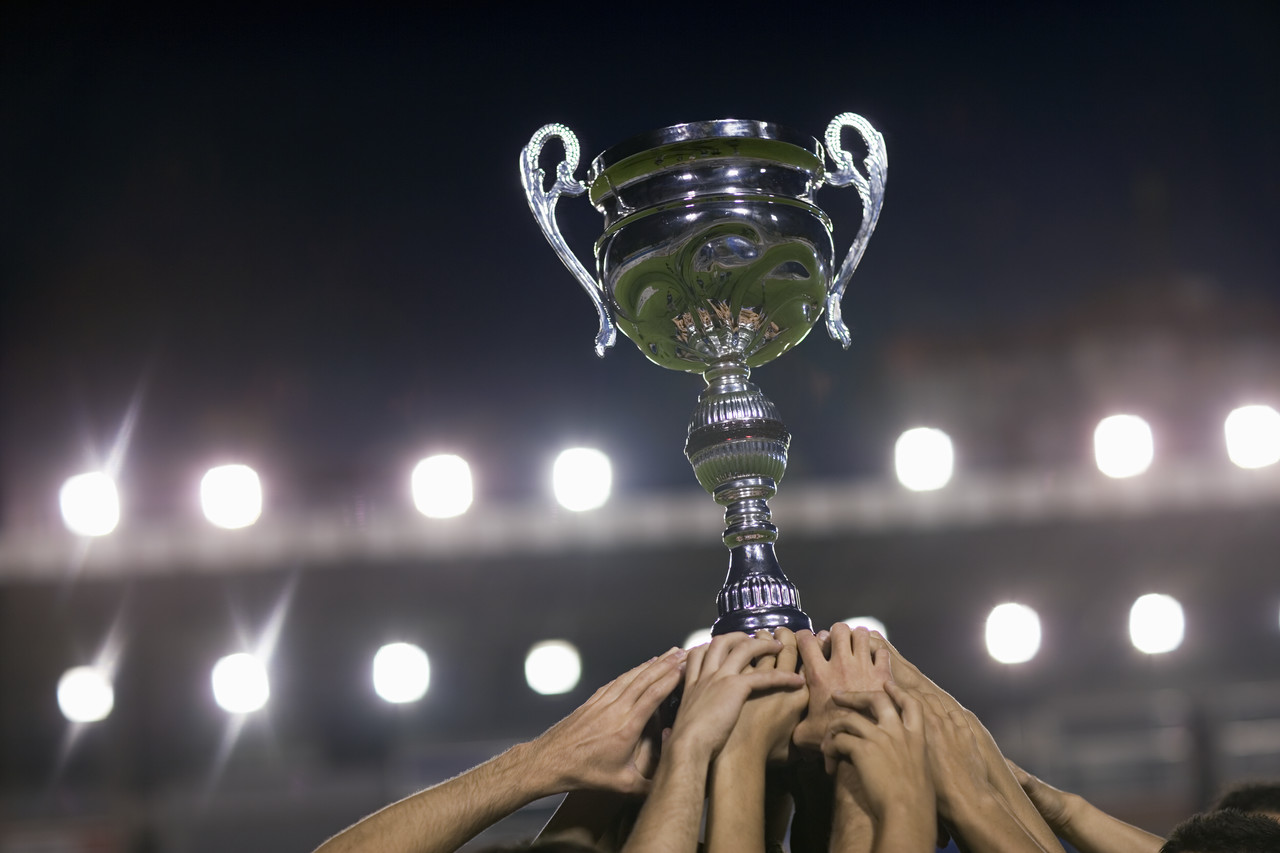 Soccer Team Raising Trophy --- Image by © Royalty-Free/Corbis